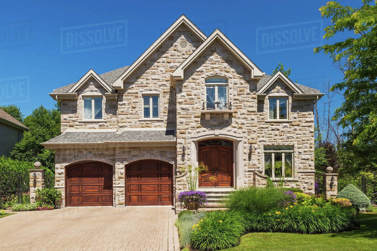 Facade of luxury house in cut stone with shrubs and flowers in garden  border stock photo