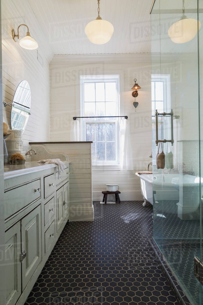 Bathroom with black tiled floor, cream paneled walls and sash windows. Stand alone white bath and glass shower cubicle. Royalty-free stock photo