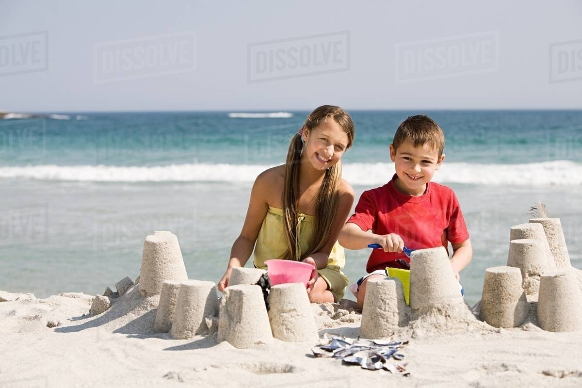 And Boy Making Sandcastles On The Beach