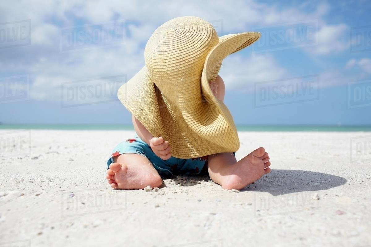 Baby boy playing with mother s sun hat on the beach - Stock Photo ... 9474ff06e0a