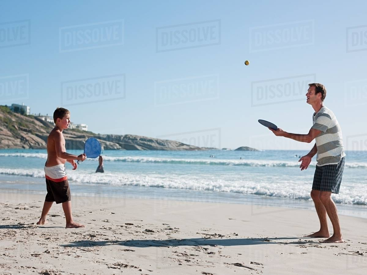 Father And Son On Playing Paddleball Beach