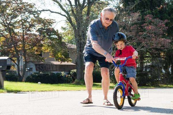 Grandfather encouraging young boy to ride bicycle Royalty-free stock photo