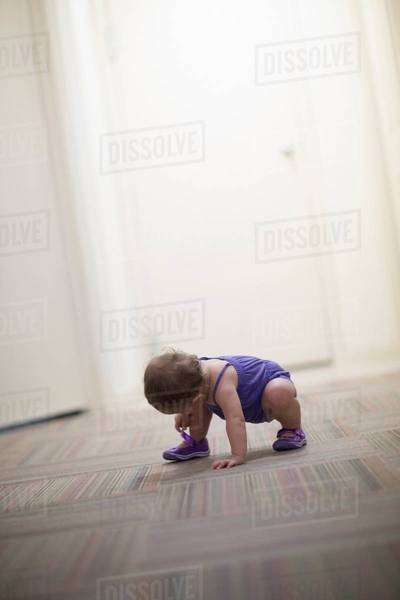 Toddler girl crouching on floor Royalty-free stock photo
