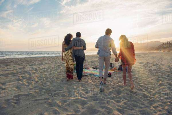Two young couples walking along beach, rear view Royalty-free stock photo