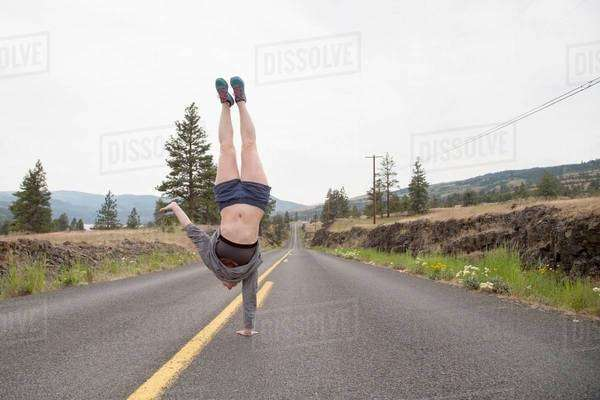 Young woman doing one handed handstand in road Royalty-free stock photo
