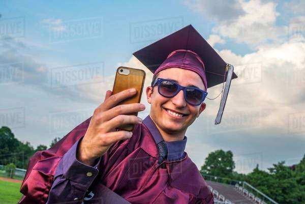 Graduate taking selfie with smartphone Royalty-free stock photo