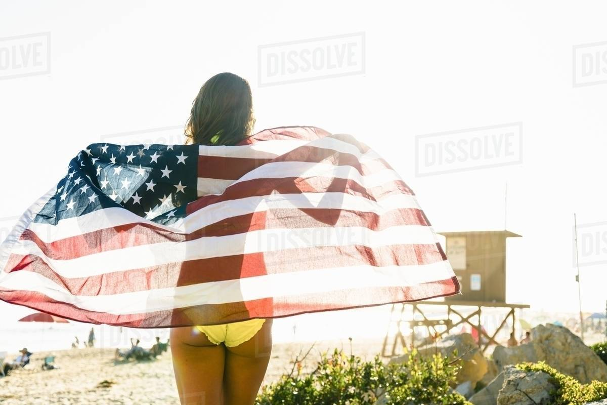 Rear View Of Young Woman Wred In American Flag On Newport Beach California Usa