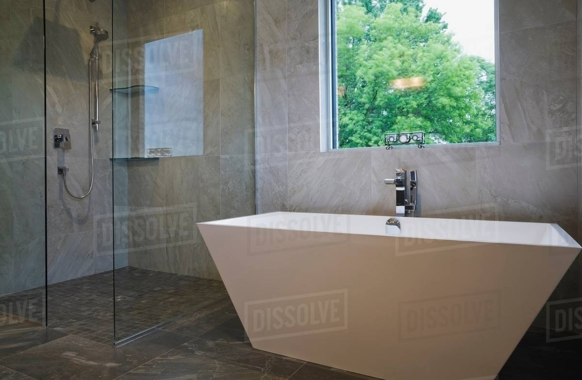 Modern bathroom with free standing bath tub and glass fronted shower ...