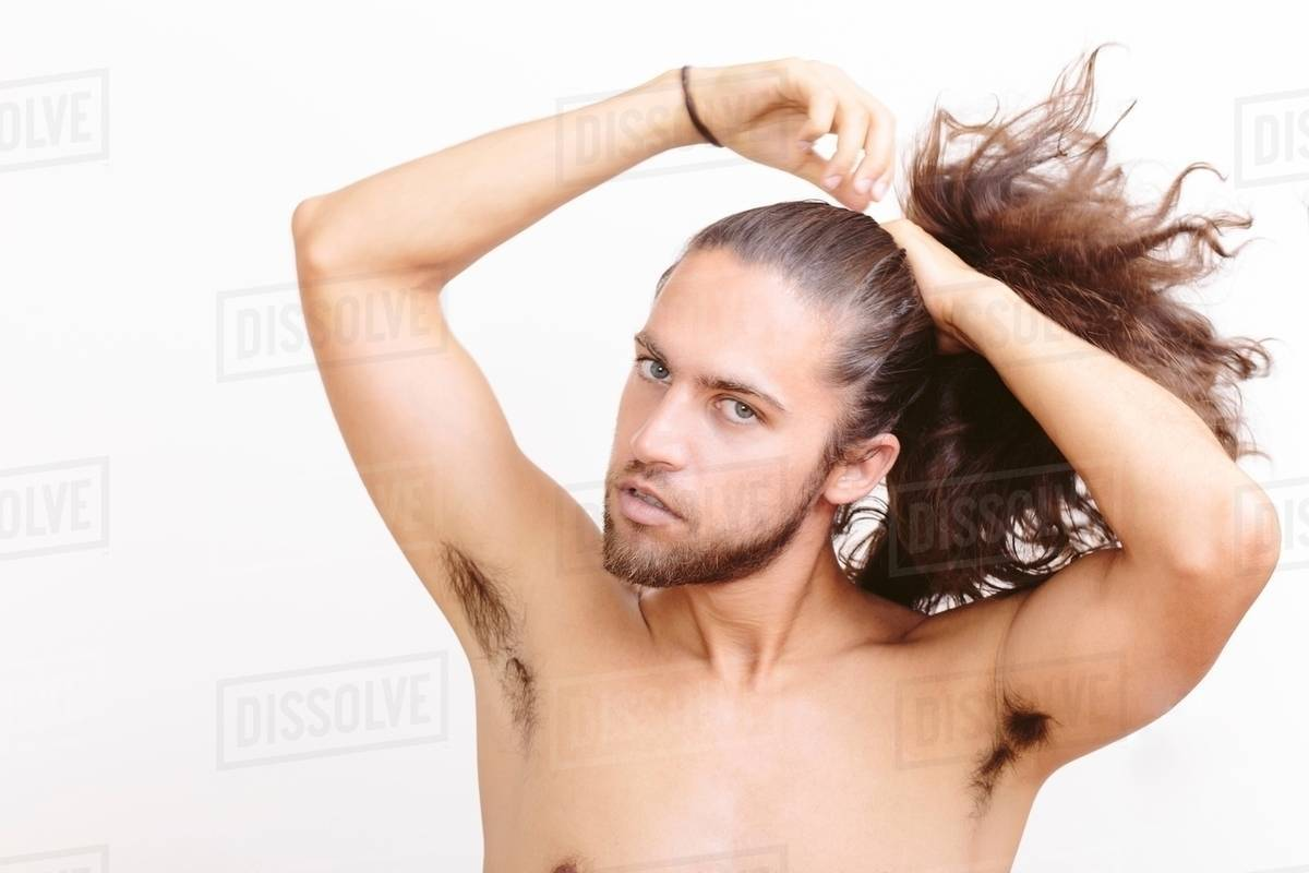 Young man with long hair, putting hair in ponytail