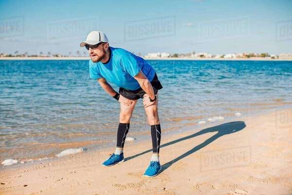 Mid adult man on coastline bending forwards looking away, Dubai, United Arab Emirates Royalty-free stock photo