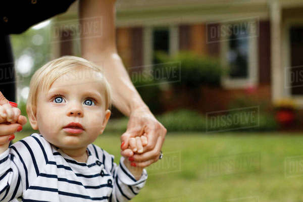 Mother holding baby girl's hands, outdoors Royalty-free stock photo