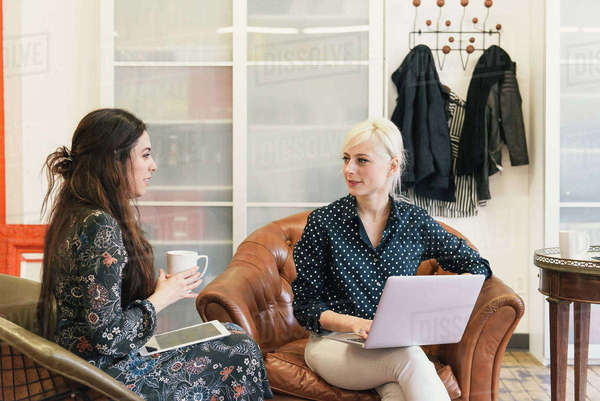 Colleagues in office sitting chatting Royalty-free stock photo