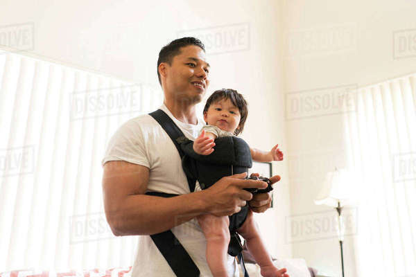 Father with baby in carrier, playing video game Royalty-free stock photo