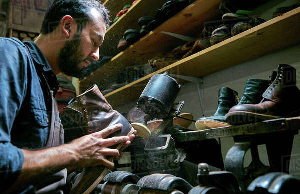 Male cobbler in traditional shoe workshop repairing boot heel Royalty-free stock photo
