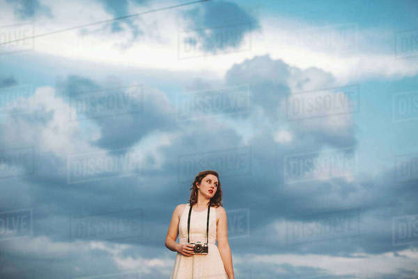 Woman against cloudy blue sky holding camera Royalty-free stock photo