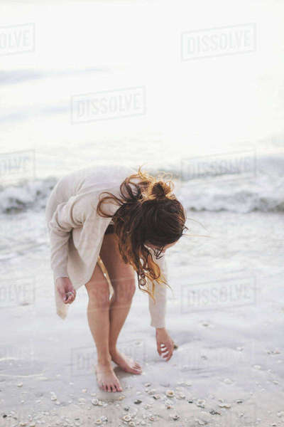 Woman picking seashells on beach Royalty-free stock photo