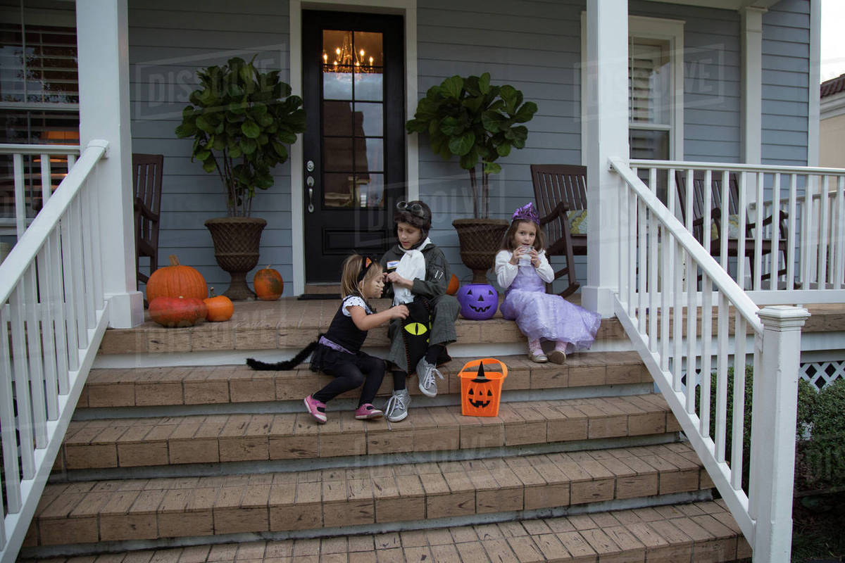 Brother and sisters trick or treating on porch stairway Royalty-free stock photo