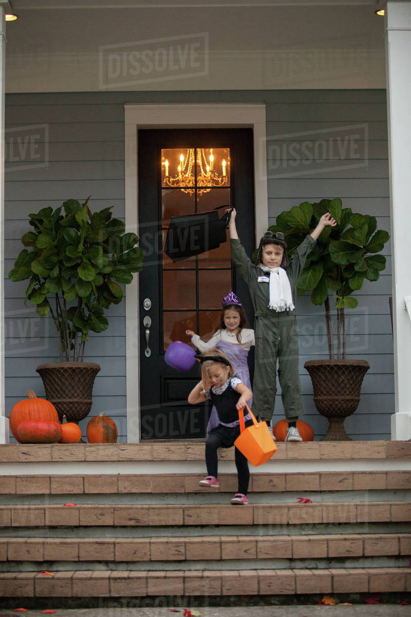 Boy and sisters trick or treating celebrating on porch Royalty-free stock photo