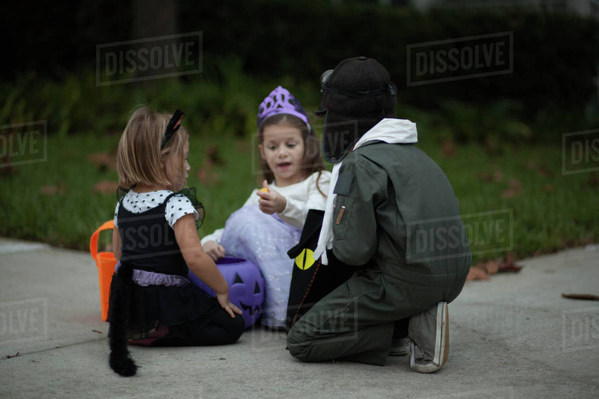 Boy and sisters trick or treating crouching and looking at treats on sidewalk Royalty-free stock photo
