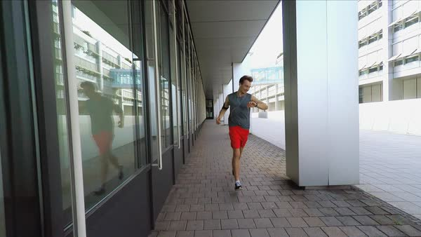 Wide, slow motion point-of-view shot of Man running in city Royalty-free stock video