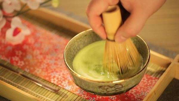 Mixing Japanese Matcha Green Tea in a Ceremonial Bowl with Whisk Rights-managed stock video