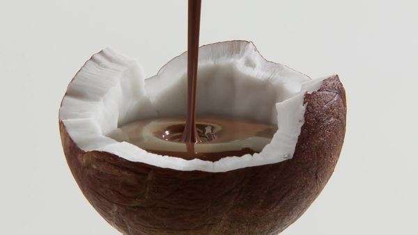 Filling half a coconut with chocolate sauce Royalty-free stock video