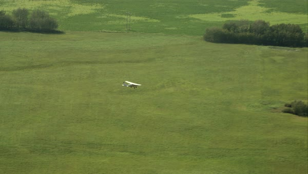 A small crop plane flying with a reveal of the farmland Royalty-free stock video