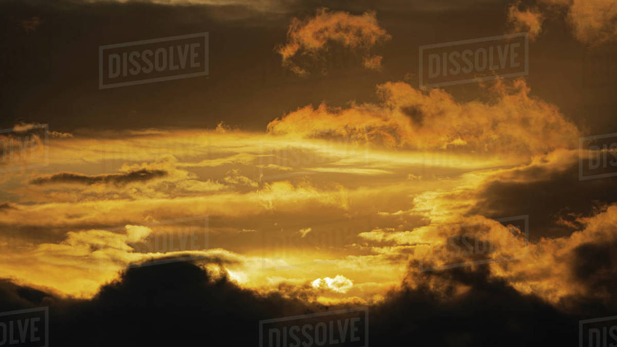 Dramatic clouds illuminated rising of sun floating in sky to change weather. Soft focus, blurred motion. Heavenly landscape image ready for design, replace sky in photo editor. Meteorology background. Royalty-free stock photo