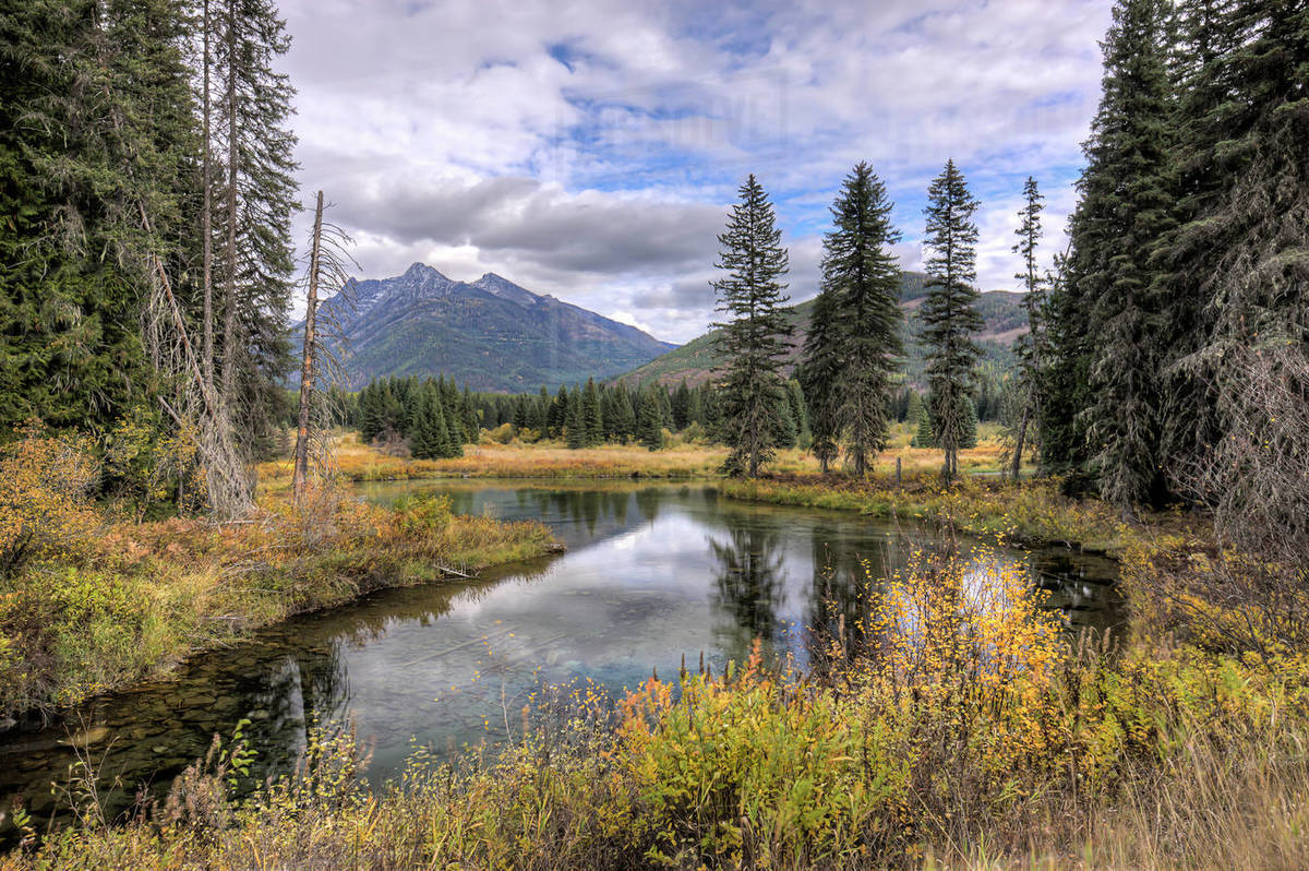 The calm Mirror Pond under a partly cloudy sky along highway 56 in western Montana Royalty-free stock photo