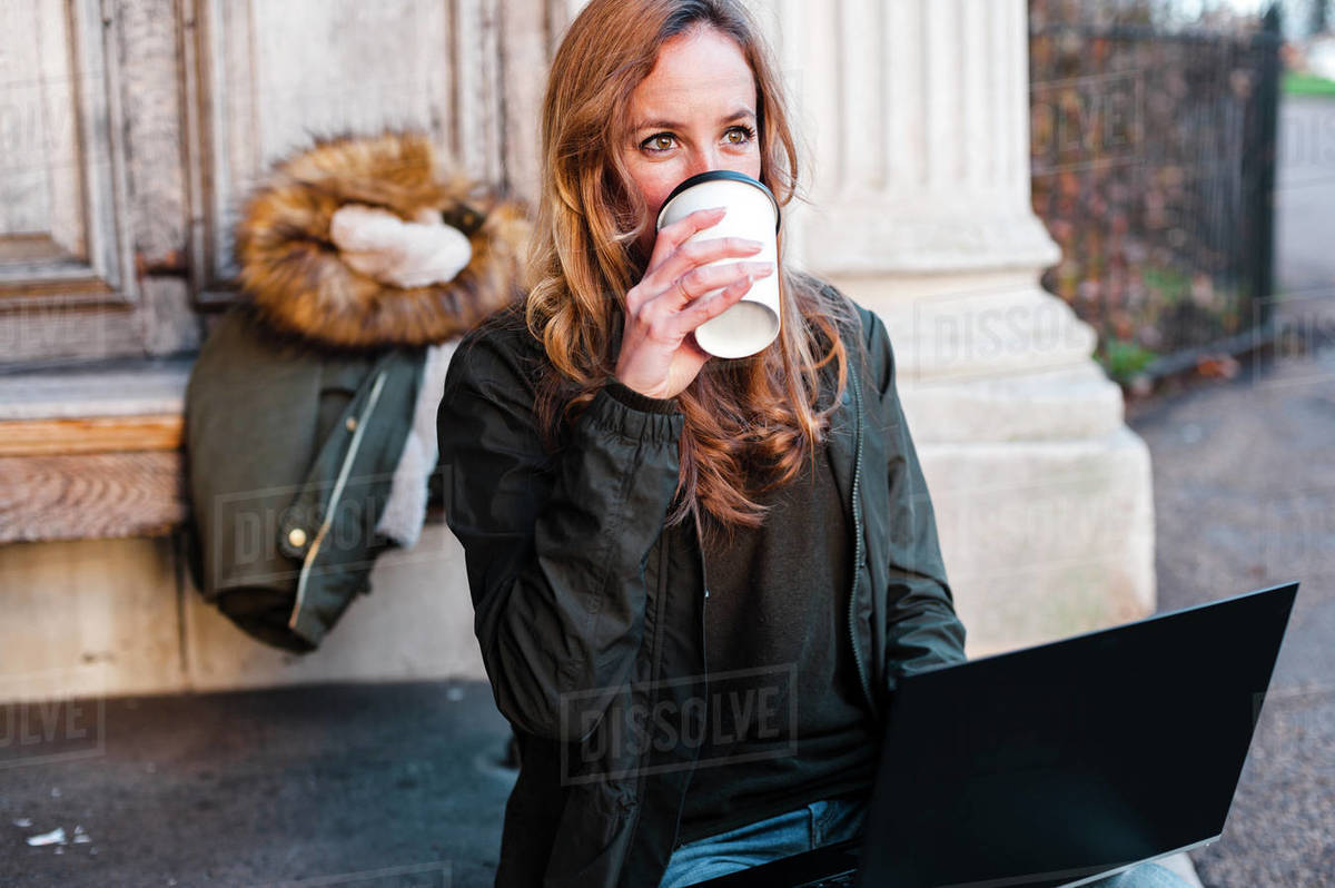 Creative businesswoman working on laptop wearing casual clothes  seated at urban park on sunny afternoon in London, UK Royalty-free stock photo