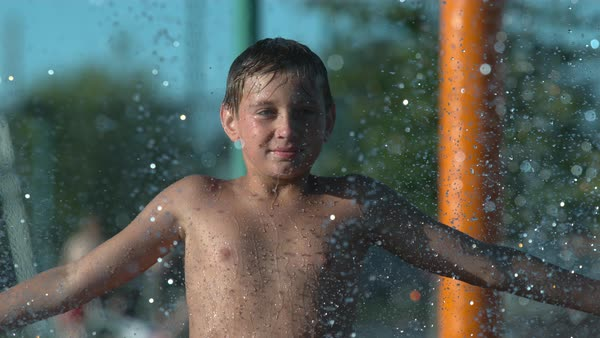 Boy playing in sprinkler at park in super slow motion Royalty-free stock video