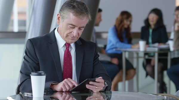 Mature businessman using digital tablet in office lobby Royalty-free stock video