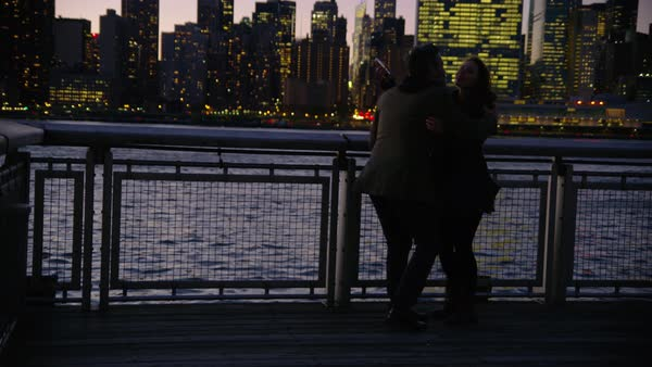 Couple in New York City standing on pier at night with city skyline in background Royalty-free stock video