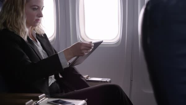Young businesswoman using digital tablet on airplane Royalty-free stock video