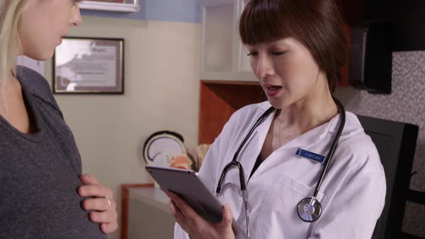 Doctor with digital tablet talks to pregnant patient Royalty-free stock video