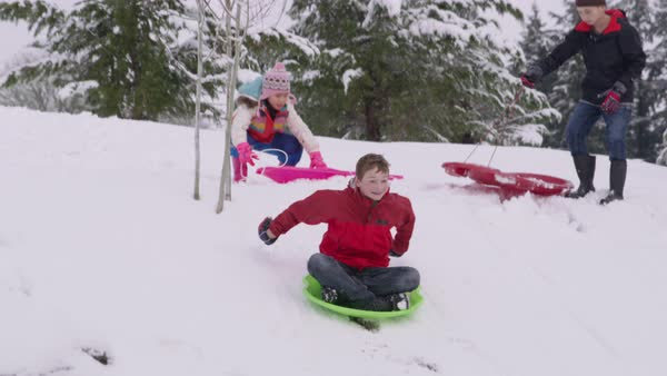 Kids sledding down snow covered hill in winter Royalty-free stock video