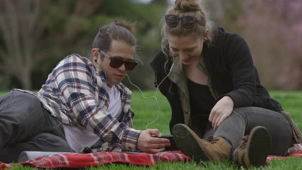 Two young people at park on blanket listening to music together Royalty-free stock video