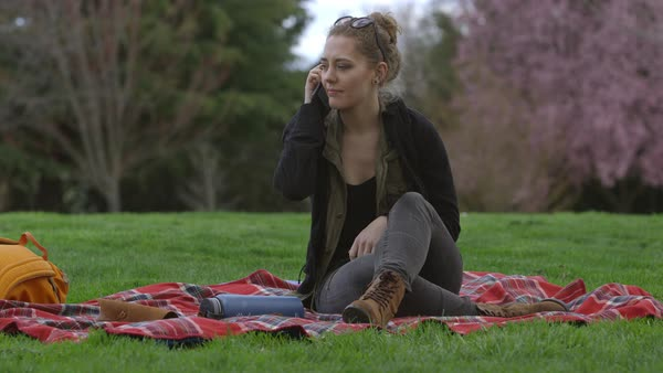 Young woman at park sitting on blanket talking on cell phone Royalty-free stock video