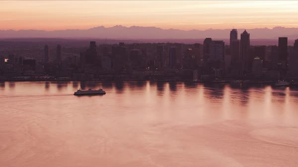 Aerial view of ferry moving towards downtown at sunrise.   Royalty-free stock video