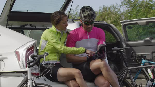 Two cyclists taking break and looking at maps on digital tablet Royalty-free stock video