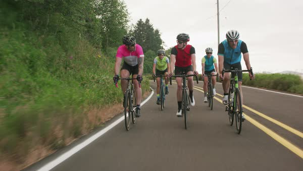 Tracking shot of a group of cyclists on country road Royalty-free stock video