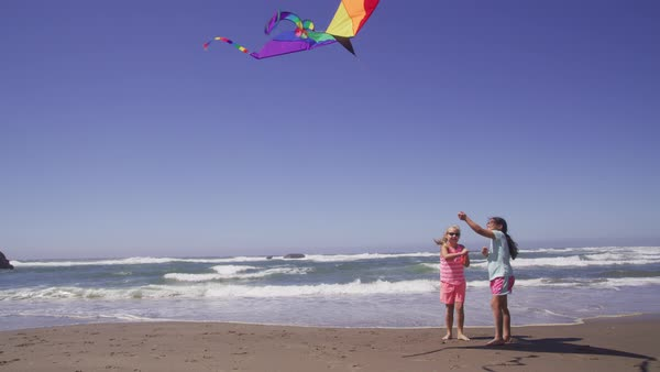 Two young girls playing with kite at beach Royalty-free stock video