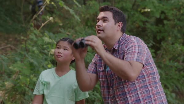 Girl at summer camp looking through binoculars with camp leader Royalty-free stock video