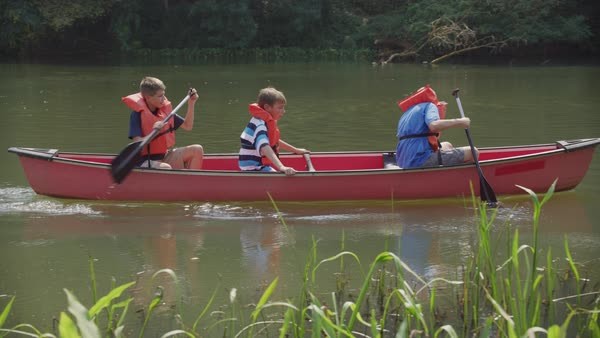Kids at summer camp paddling a canoe Royalty-free stock video