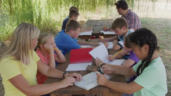 Kids at outdoor school writing in notebooks Royalty-free stock video