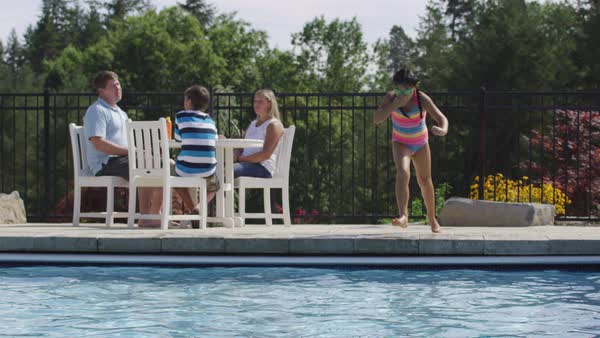 Girl jumping into backyard pool Royalty-free stock video