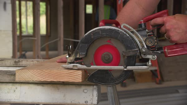 Closeup of construction worker cutting with circular saw Royalty-free stock video