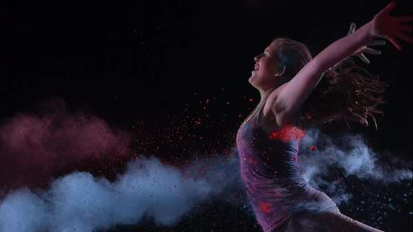 Colored powder hitting girl as she runs, slow motion. Royalty-free stock video