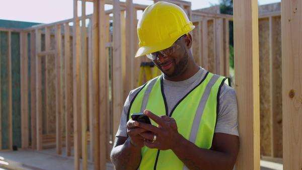 Construction worker texting on cell phone Royalty-free stock video