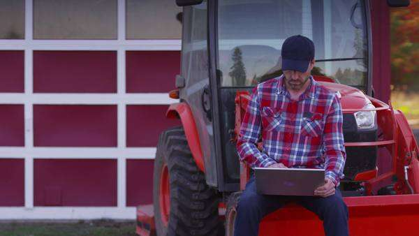 Farmer sits on tractor using laptop computer Royalty-free stock video